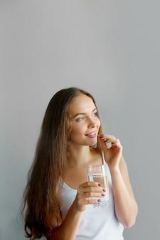 健康的な食事、ライフスタイル。ピルを服用している幸せな笑顔の女性のクローズアップ