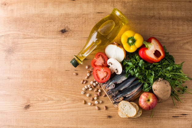 Healthy eating. mediterranean diet fruit,vegetables, grain, nuts olive oil and fish on wooden table