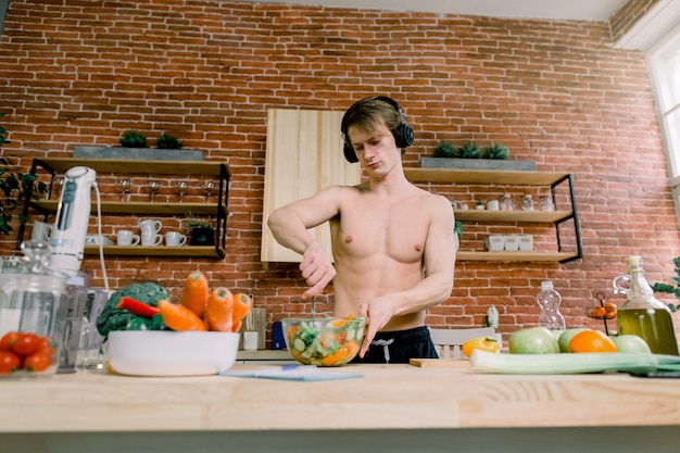 Healthy eating and nutrition supplements. handsome male listening to music and dancing while preparing a salad enjoying sports drink in kitchen. bodybuilding concept
