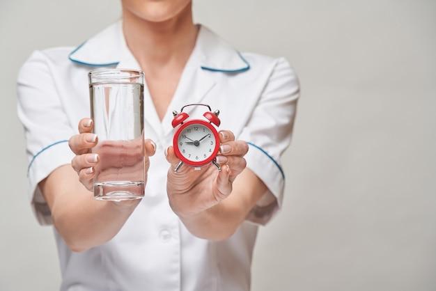 Концепция здорового питания или образа жизни - женщина-врач держит стакан чистой свежей воды и маленький красный будильник