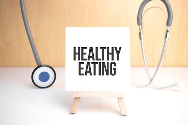 Знак здорового питания на небольшой деревянной доске на мольберте с медицинским стетоскопом