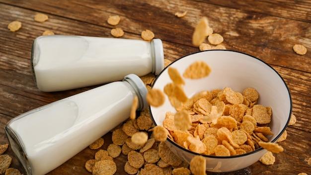 健康的な食事の表面。ドライフレークはボウルと2本のミルクに落ちます。