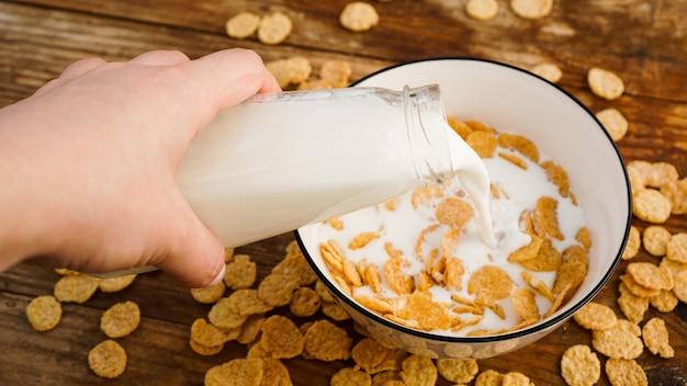健康的な食事の表面。コーンフレークのボウルに新鮮なミルクを注ぐ。