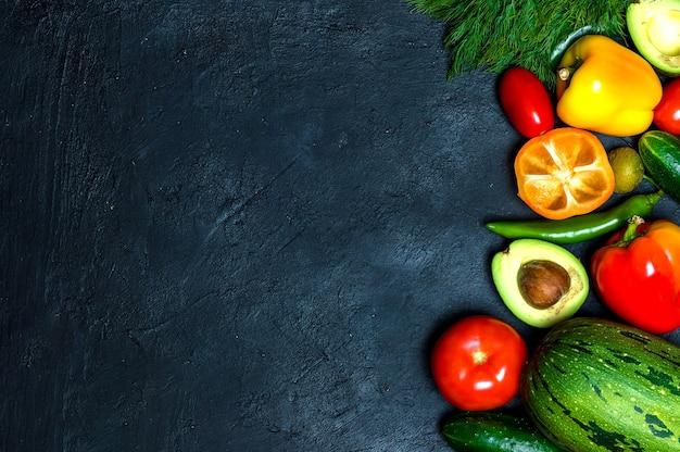 健康的な食事。野菜と果物。黒の背景に。上からの眺め。スペースをコピーします。