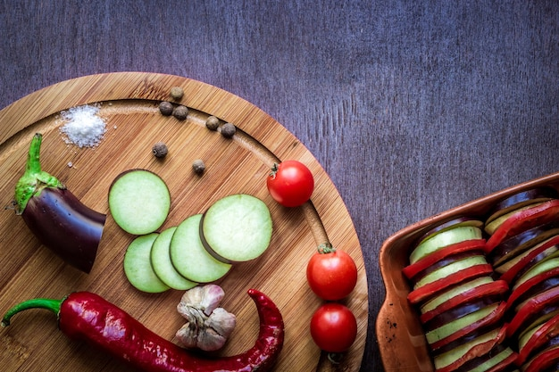 オリーブオイルのスパイスでオーブンで焼くために準備された健康的な食事の菜食主義の食糧生のナス
