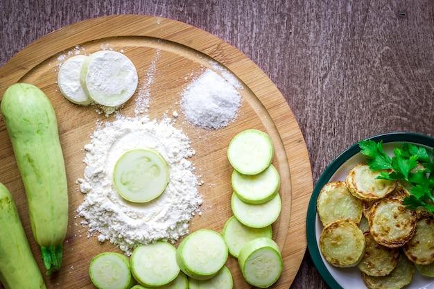 健康的な食事、ベジタリアン料理。生のズッキーニは、オリーブオイルにスパイスを入れたフライパンで揚げるために用意されています。上面図。木製の背景。スペースをコピーします。静物。フラットレイ