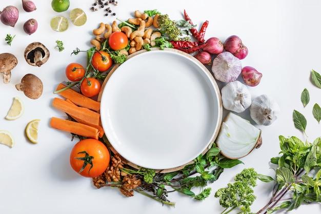 Здоровое питание. белое блюдо в окружении здоровых свежих овощей