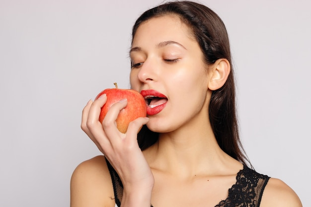 Healthy eating. woman biting red apple with perfect teeth over grey background