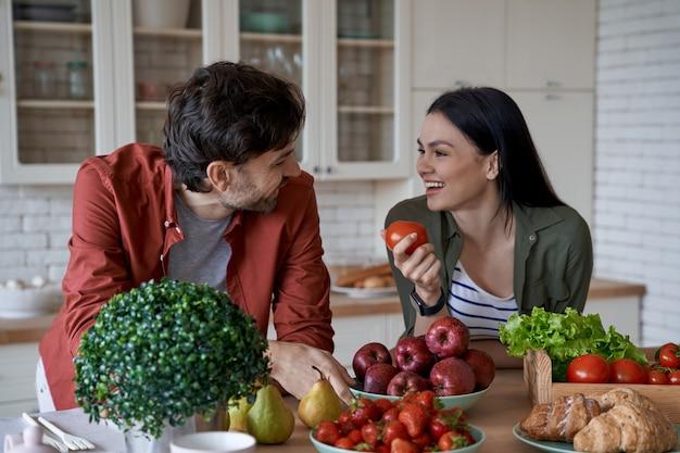 新鮮なトマトを保持し、彼女の夫を見ながら健康的な食事の若い美しい女性
