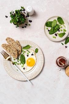 Здоровый яичный завтрак со шпинатом и микрозеленью, вид сверху на мраморном столе