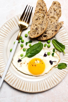 Healthy egg breakfast with spinach and microgreens, top view on marble table