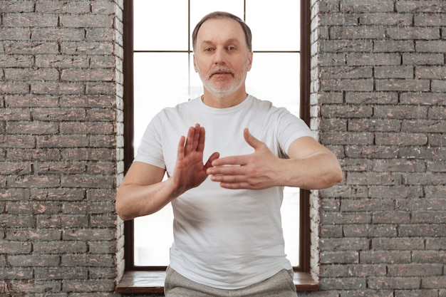 Healthy elderly sportsman wearing white t-shirt keeping arms bent in elbows looking on camera