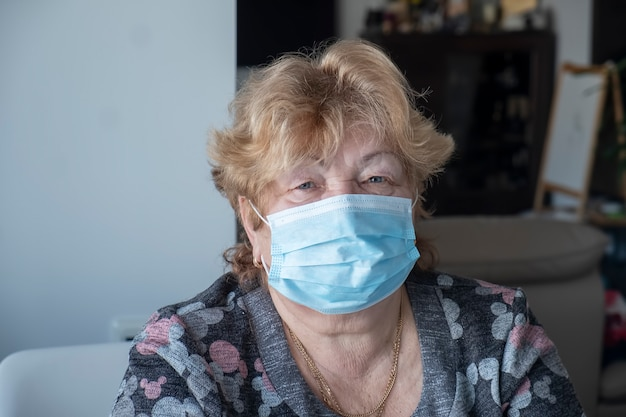 Healthy elderly woman in blue medical protective mask looking at camera.