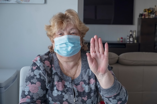 Healthy elderly woman in blue medical protective mask showing gesture stop. coronavirus outbreak