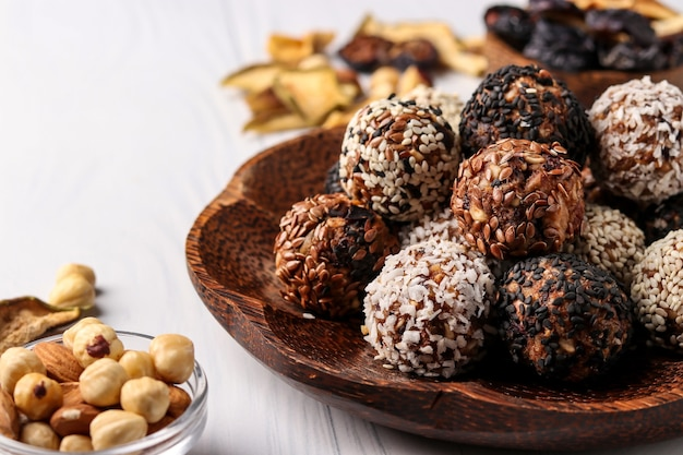Healthy energy balls of nuts, oatmeals and dried fruit with coconut, flax and sesame seeds on coconut wooden plate on a white background, horizontal orientation, copy space, closeup