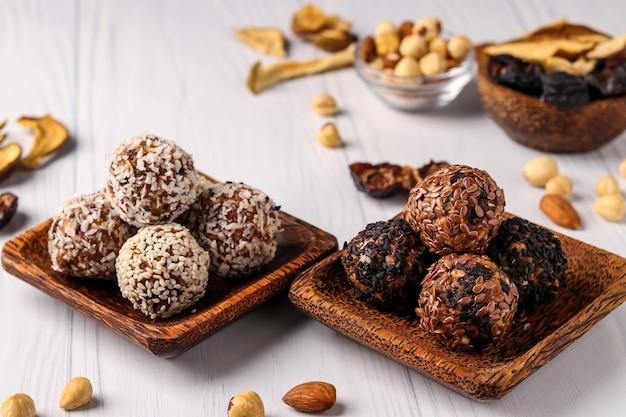 ナッツ、オートミール、ドライフルーツの健康的なエネルギーボール、白い表面の木製ココナッツプレートにココナッツ、亜麻、ゴマの種子、水平方向、クローズアップ