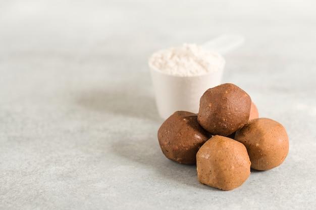 Здоровые энергетические сырые протеиновые шарики на светло-сером столе, фитнес-десерты, закуски