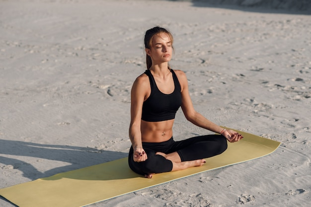 Healthy energy woman balance body and practicing yoga and meditate on the beach in the sand. healthy concept