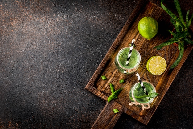 Healthy exotic detox drink aloe vera or cactus juice with lime on dark background
