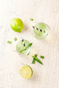Healthy exotic detox drink, aloe vera or cactus juice with lime, on light concrete background