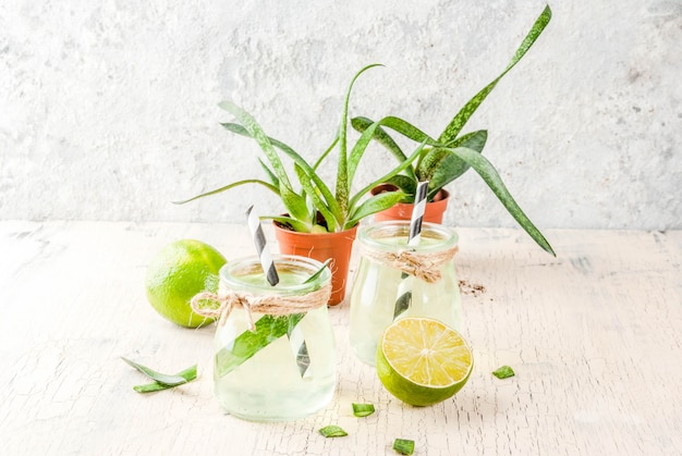 Healthy exotic detox drink aloe vera or cactus juice with lime on light concrete background