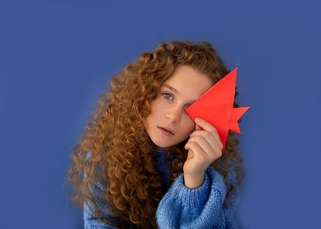 10代の髪の毛の少ない女の子の健康な目、折り紙の魚は目を閉じます。健康ビジョン光学コンセプト。クローズアップ写真
