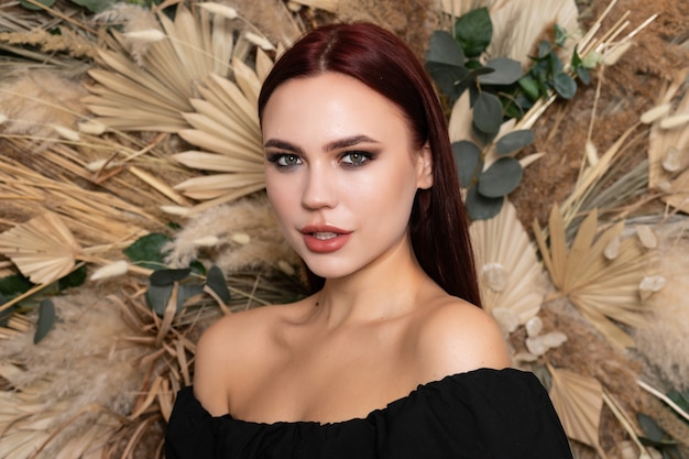 Healthy face skin care beauty, middle age skincare cosmetics, cosmetology concept. brunette girl with burgundy lips on a background of spring dry field flowers. open shoulders