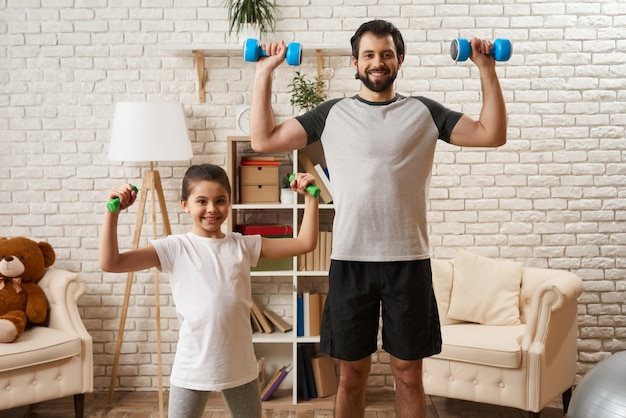 Healthy family doing exercises with dumbbells.