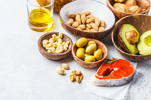 Healthy fat food background. fish, nuts, oil, olives, avocado on white background.
