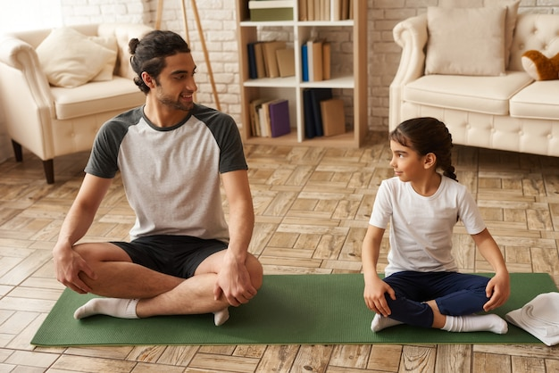 Healthy father and daughter sit in lotus pose on carpet.