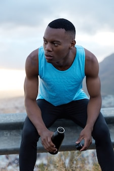 Healthy fatigue dark skinned man takes break after outdoor workout, holds bottle of energy drink, has pensive look aside, models outside alone, refreshes with water, tries to rejuvenate, being strong