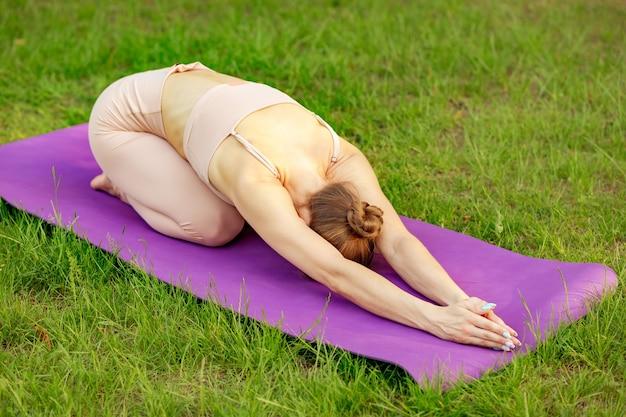 Здоровая женщина на коврике для йоги, расслабляя ее разум, тело