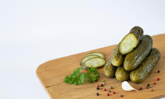健康的な発酵スライスガーキンやキュウリのハーブとスパイスを白で隔離される素朴な木の板に