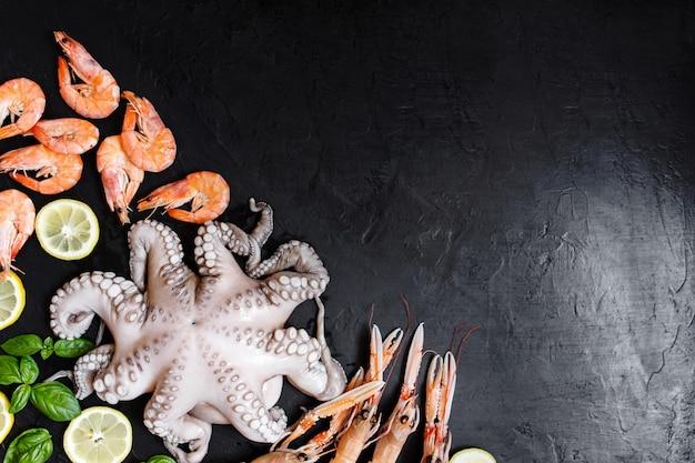 Ассортимент здоровой рыбы и морепродуктов на черном фоне. вид сверху. морепродукты на черном деревенском фоне.