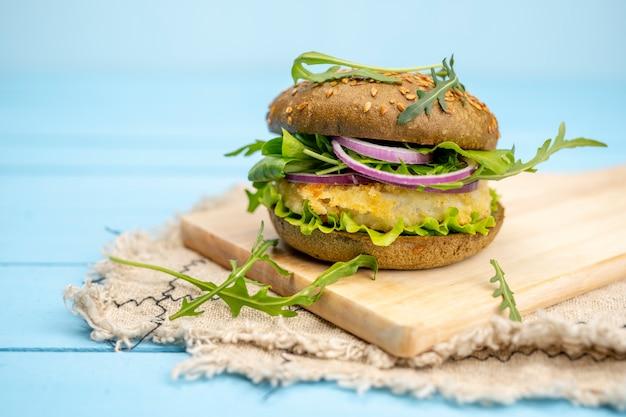 青い背景にルッコラと健康的な魚のハンバーガー。