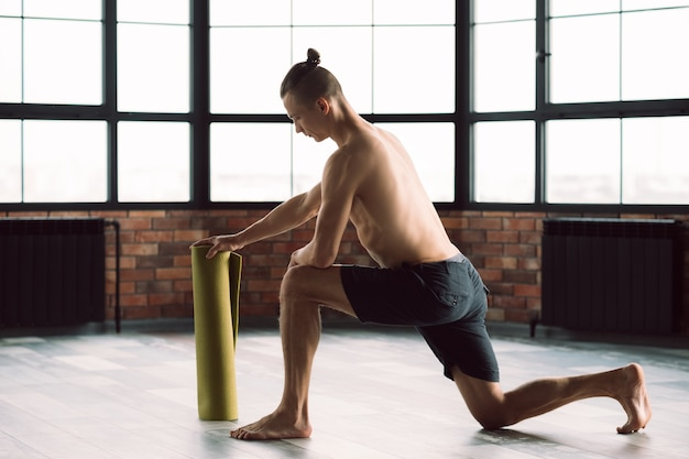 Healthy and fit body. gym training. active lifestyle. man preparing to exercise on a yoga mat.