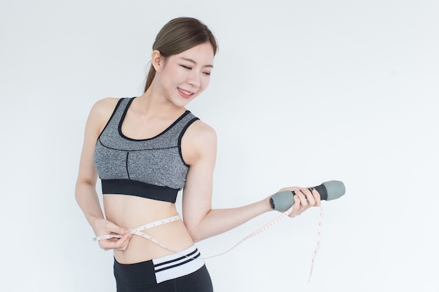 Healthy fit and firm asian woman measuring her waist looking at measuring tape