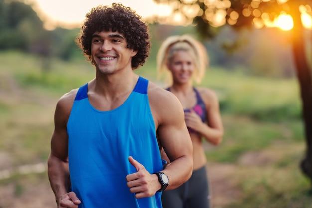健康的なフィット動機スポーティなカップルが早朝に公園で走っています。