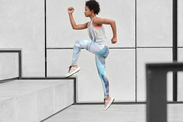 건강한 여성은 계단을 오르고, 편안한 옷과 트레이너를 입고, 조깅 운동을하고, 도시 환경에서 스포츠를하고, 빠르고, 옆으로 포즈를 취합니다. 웰빙과 결단력 개념
