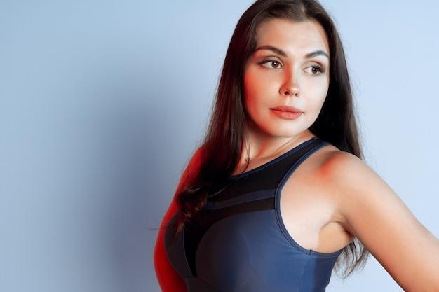 Здоровая подтянутая молодая женщина в спортивной одежде, стоящая на сером фоне