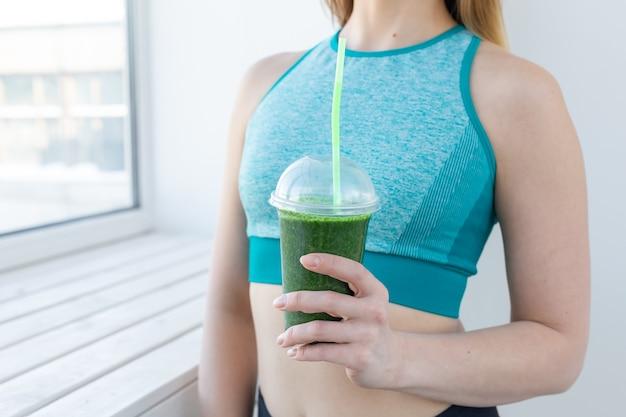 健康、フィットネス、デトックスの概念-緑のスムージーとスポーツウェアの若い女性のクローズアップ