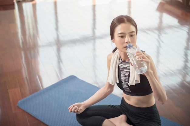 Healthy and fitness concept. beautiful sport woman take a rest with drinking after workout at gym.