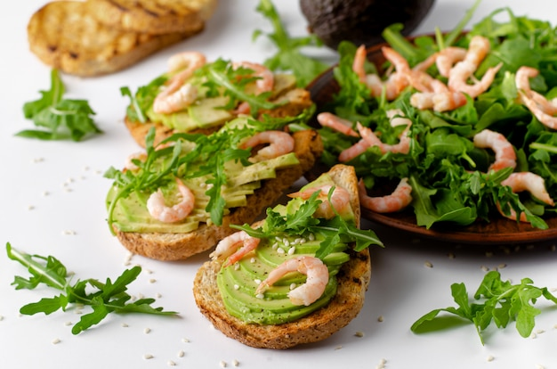 Healthy fitness food. toasts with avocado, shrimps and arugula salad on white background