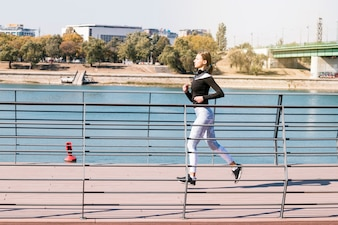 Healthy fitness sporty female runner running near the lake