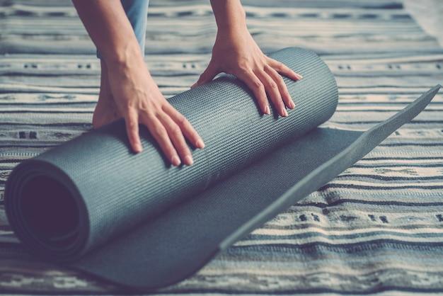 健康なフィットネスの女性は、リビングルームの床で運動した後、マットを巻き上げる手、自宅で運動をしている女性。自宅の床でヨガマットを転がしたり広げたりする女性の手