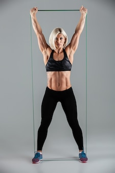 Healthy fitness woman with raised arms stretching with elastic rubber