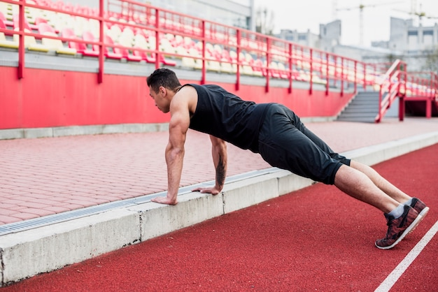 Healthy fitness young man on race track doing pushups