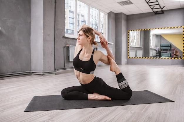 スポーツ スタジオでヨガを楽しんでいる健康で柔軟な女性