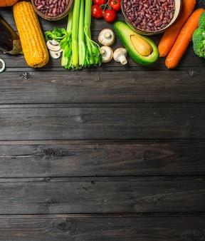 健康食品。さまざまな有機果物や野菜、豆類、シリアル。木製の背景に。