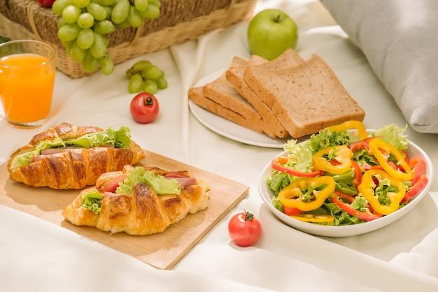 Здоровая еда и аксессуары для летнего или весеннего пикника на открытом воздухе, плетеная корзина для пикника со свежими фруктами, хлебом и стаканом освежающего апельсинового сока на фоне природы кемпинга.